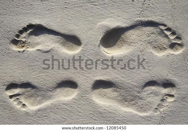 Fun four footsteps on a coral sandy beach