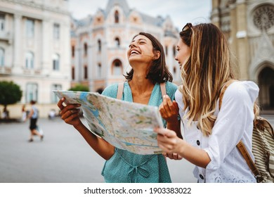 Fun, friends, travel and tourism concept. Beautiful girls looking for direction in the city - Shutterstock ID 1903383022