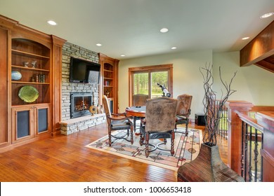 Fun game area on the second floor. Poker table surrounded by chic gray leather chairs facing stone wall fireplace flanked by built in bookshelves.  Northwest, USA