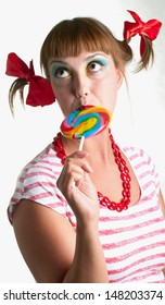 Fun girl with  candy on light background. Shallow DOF.