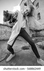 fun girl with gun screaming aiming at camera, monochrome image