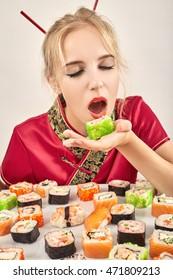 fun girl in the Japanese dress eats sushi