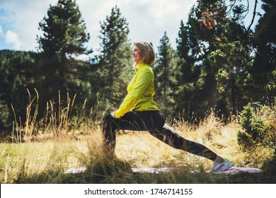 Fun girl one exercising outdoors in green forest sun summer day, activity with stretch legs. Smile fitness woman stretching exercises training outside. Sportswoman isolaition in nature