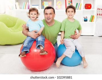 Fun with gymnastic balls - young boys playing with their father