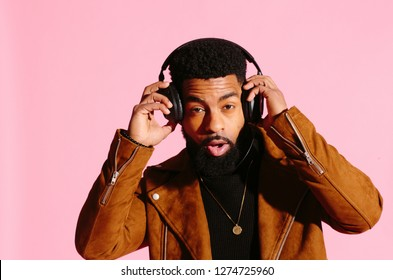 fun, handsome and cool African American man with beard, listening music, looking at camera, isolated on pink studio background