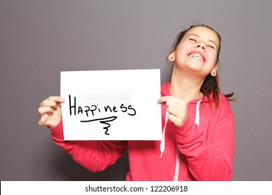 Fun Happiness concept with a young girl holding up a handwritten sign saying Happiness and tilting her head back with a cheeky ear to ear grin