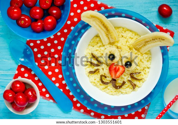 Fun and healthy breakfast idea for kids - Easter bunny millet porridge with milk, sugar, chocolate, banana and strawberry