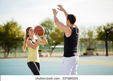 Fun Hispanic couple playing basketball against each other and having lots of fun
