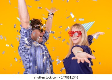 Fun, holidays and party concept - Couple dancing among falling confetti on yellow background