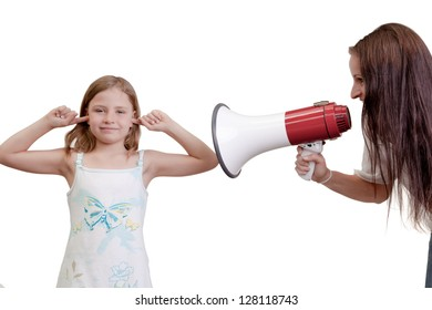 Fun humorous image of a naughty little girl playing deaf sticking her fingers in her ears while her mother shouts at her with a megaphone isolated on white