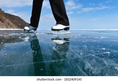 Fun ice skating on a frozen lake on a sunny winter day. View of the beautiful transparent blue ice of frozen Baikal Lake. A girl in white figure skates travels on the ice. Winter outdoor activities