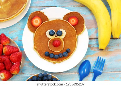 Fun idea for kids breakfast. Bear shaped pancakes with berries on blue wooden table, top view. Healthy food for children. Funny food for kids