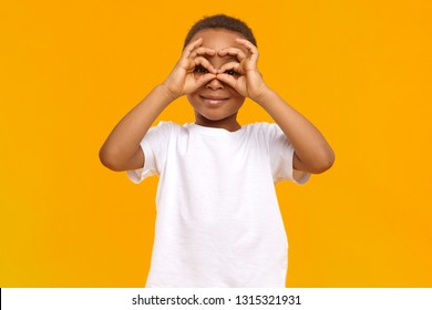 Fun, joy, leisure and happy childhood concept. Dark little boy in casual white t-shirt making mask, holding hands at his eyes, connecting thumbs and index fingers as if looking through binoculars