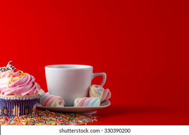 Fun kid breakfast. Colored cupcake with tea cup on brigthplain red background