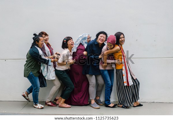 A fun and light hearted group portrait of a diverse team of women from different cultures and ethnicities. They are standing close to one another and tickling each other and laughing and having fun.