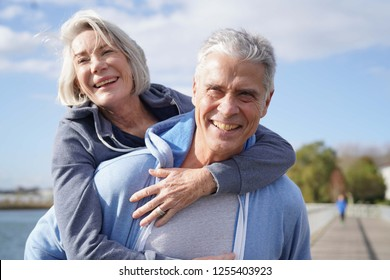 Fun loving senior couple piggyback riding outdoors