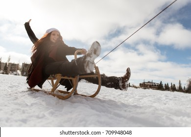 Fun loving woman sledging in winter park