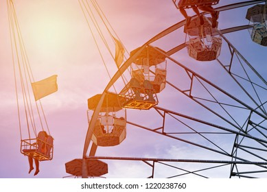 fun in the lunapark, people on the rollercoaster and big wheel, susnet