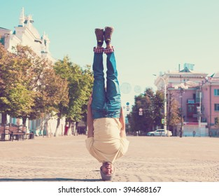 Fun man dancing. Has yellow t-shirt, blue jeans, slim sport body. Motion on great urban city. Amazing portrait. Sports acrobatic handstand. Fitness concept. Cool jump. Head over heels. quest