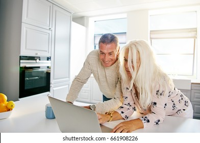 Fun middle aged couple looking at laptop computer on counter top in spacious bright kitchen