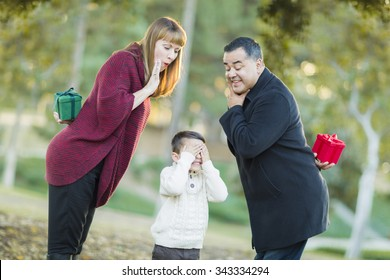 Fun Mixed Race Parents With Gifts for Young Boy Hiding His Eyes.