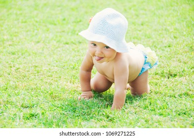 Fun mood. Cute little girl sitting on the grass on a sunny summer day