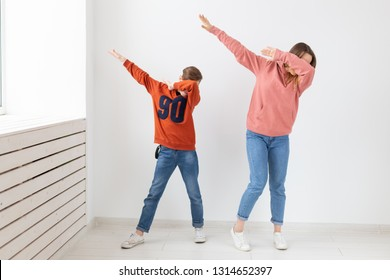 Fun, mothers day, children and family concept - teen boy and his mom funny dancing on white background