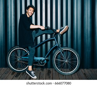 Fun. Night portrait with a flash of a young man in a fashionable black outfit, put one foot on the wheel of a vintage bicycle. Outdoor.