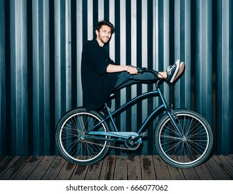 Fun. Night portrait of a young man in a fashionable black outfit, laid his feet on the steering wheel of a vintage bicycle. Outdoor.