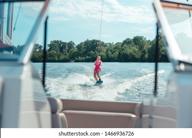 Fun outdoors. Happy blonde girl riding a wakeboard on a local river while following behind a motorboat