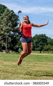 fun outdoors selfie - thrilled young blond woman jumping with cell phone on stick for happy self-portrait in park, sunny day in summertime