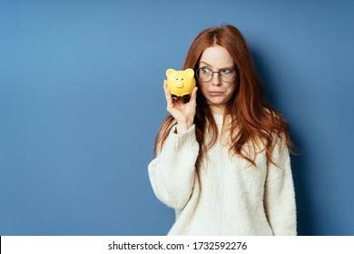 Fun photo of a young woman eyeing her piggy bank with a dismal sideways glance of dismay as she holds it to her cheek on a blue studio background with copy space