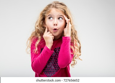 Fun playful little blond girl with a teasing expression exclaiming Ooh holding her hands to her head as she glances up to the side