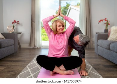 Fun playful older couple at home exercising yoga together, healthy lifestyle, husband being funny as a distraction