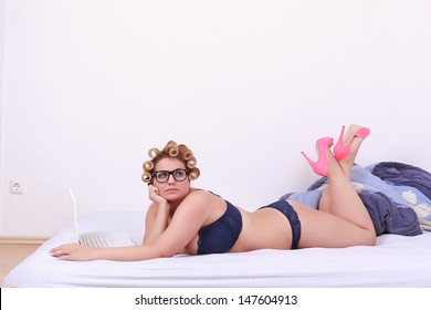 Fun portrait of a beautiful plus-size model in lingerie lying on her stomach with her hair in curlers kicking her feet in the air clad in pink stilettos / Fun portrait of a plus-size model in lingerie