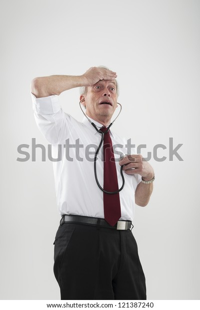 Fun portrait of a hypochondriac man worried by his health with one hand to his forehead while listening to his heart using a stethoscope with the other, or as a warning of heart disease in the elderly