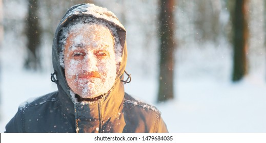 Fun portrait of a young frozen man jogging in a blizzard in new york woods. snow and frost covered face. Closeup portrait of happy young guy smiles in cold weather run in winter nyc forest at sunset.