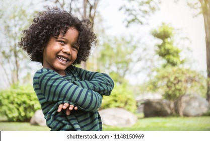 Fun in the spring park. Portrait of young happy little afro black boy stand on green grass background. Education back to school spend leisure time in nature forest, authentic concept