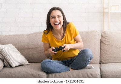 Fun stay home pastimes. Excited Hispanic woman with controller playing video games on sofa indoors