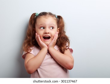 Fun surprising kid girl with open mouth and big eyes looking on empty copy space