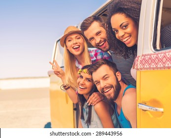 Fun time with friends. Group of happy young people smiling at camera while sitting inside of retro mini van