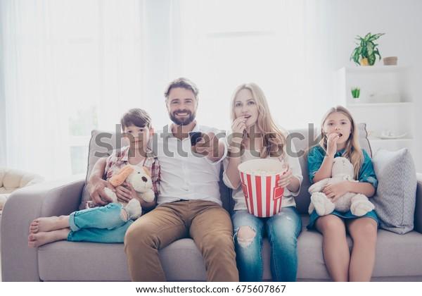 Leuke tijd samen. Gelukkige familie van vier kijkt naar interessante educatieve documentaire, het eten van popcorn, thuis op een bank