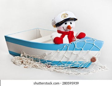 Fun toy snowman in a wooden boat with a fishing net on a white background