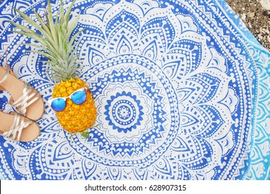 Fun tropical hipster beach layout on round mandala towel in the sun with pineapple wearing trendy mirrored sunglasses with gold sandals