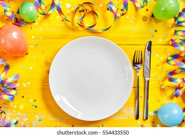 Fun vibrant carnival table setting with an empty white plate and cutlery on a bright yellow wood background with a border of party streamers and balloons