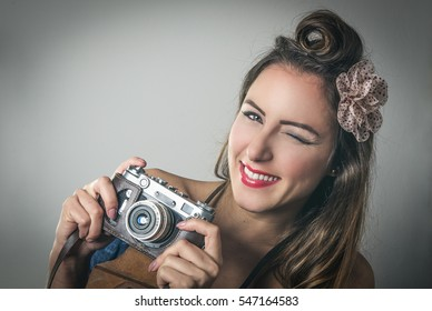 Fun vivacious retro fashion photographer with her hair in a French roll adorned with a flower winking at the camera with a beaming smile