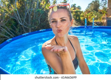 Fun weekend alfresco. Portrait of cheerful active woman in blue swimwear in the swimming pool blowing air kiss