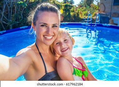 Fun weekend alfresco. smiling active mother and daughter in beachwear in the swimming pool taking selfie