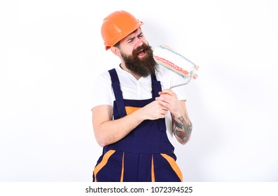 Fun at work. Bearded man in orange protective helmet using paint roller as microphone. Young builder singing rock song isolated on white background .