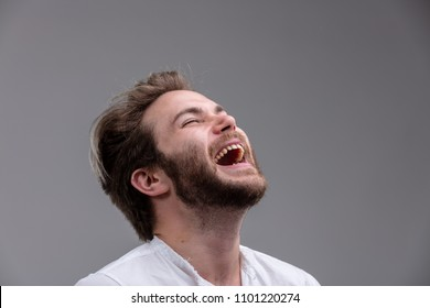 Fun young man with a sense of humour enjoying a hearty laugh with his head thrown back and mouth open isolated on grey